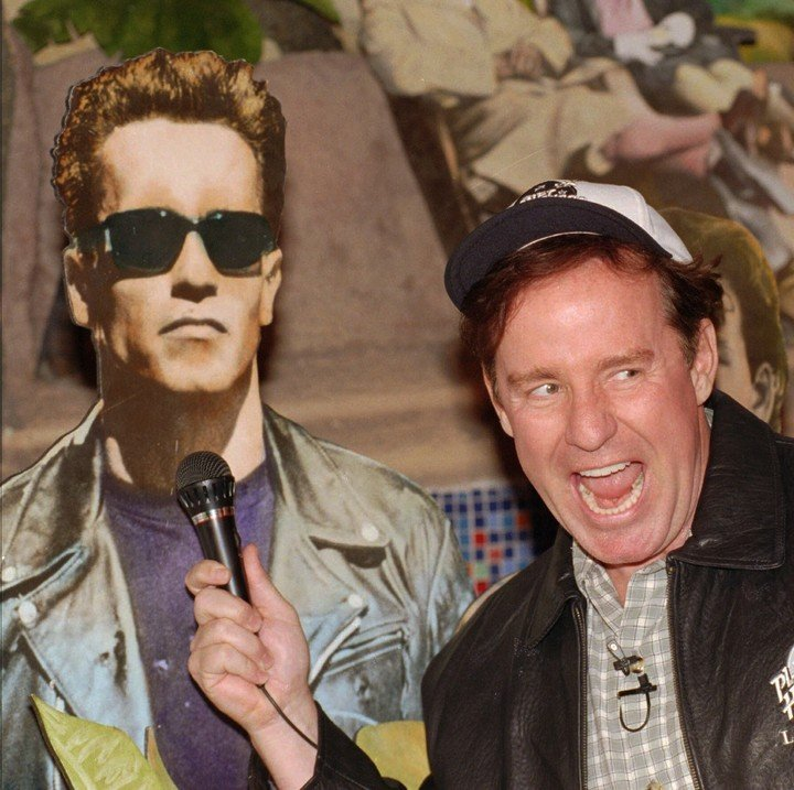 Hartman alongside a photo of Arnold Schwarzenegger, with whom he worked on The Promised Gift. Photo: AP.