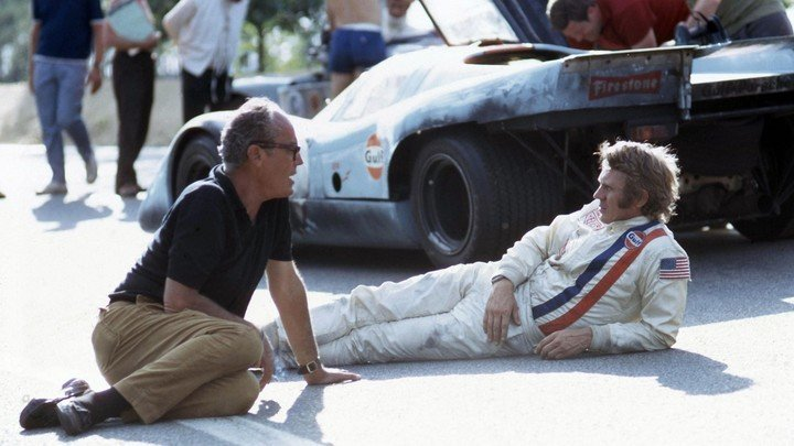 Steve McQueen, lying on the ground, during the Le Mans filming, with a Porsche 917K in the background.