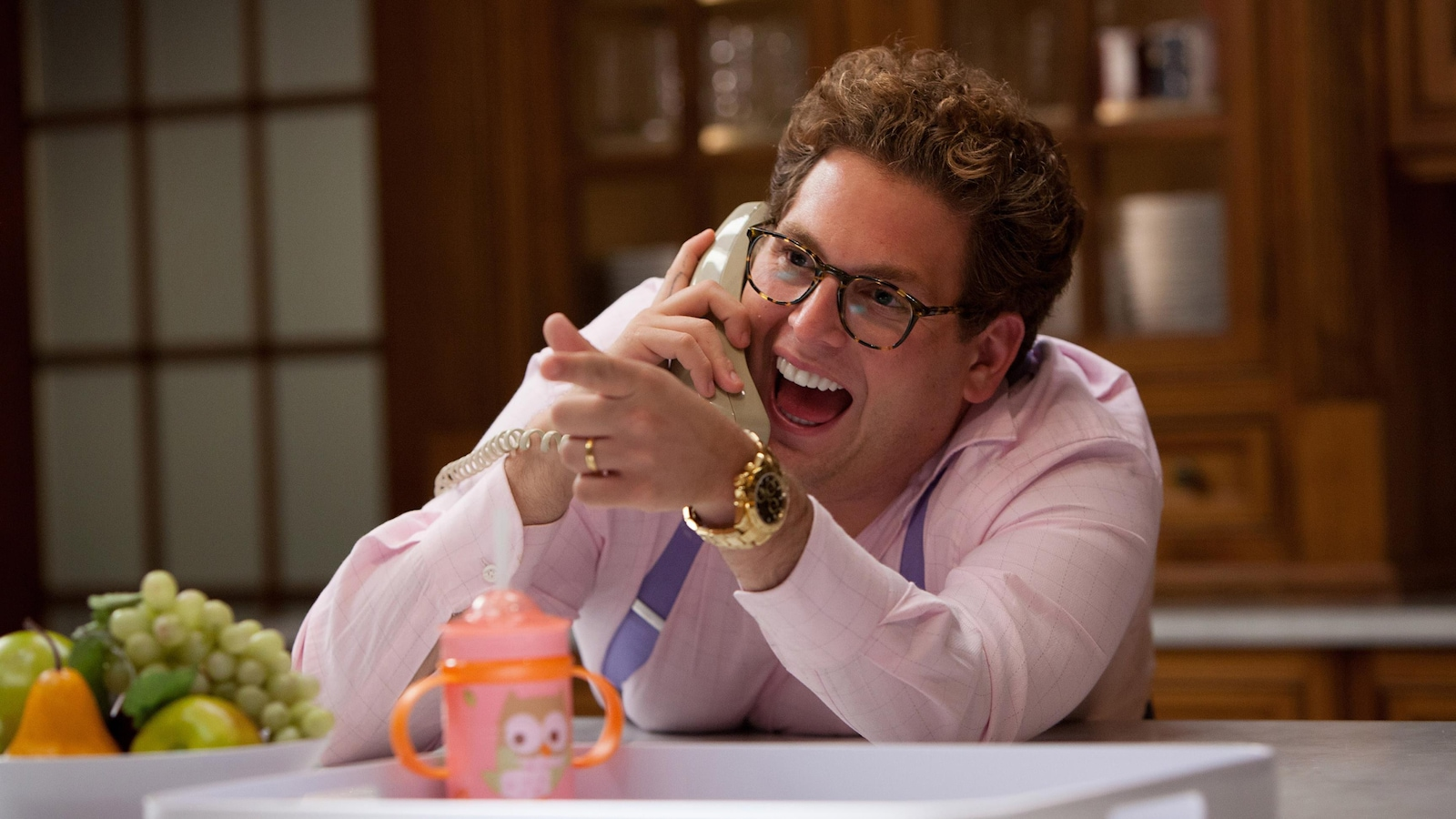 A man (Jonah Hill) wearing glasses and a gold watch laughs with his mouth open on the phone.