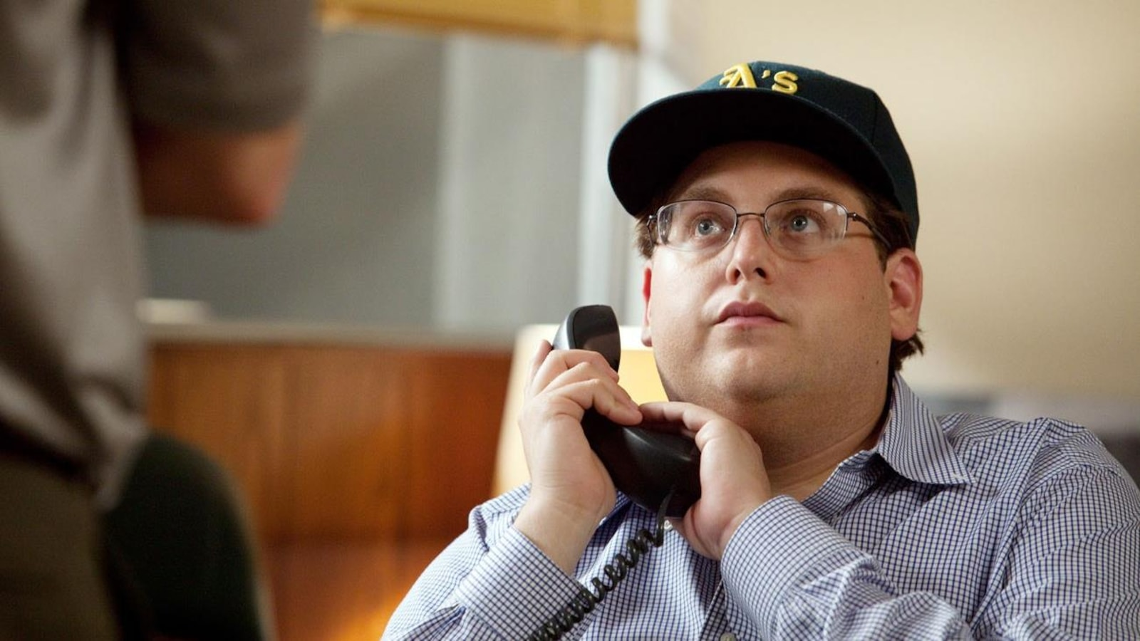 A man (Jonah Hill) with a cap, one hand on the receiver of his phone.