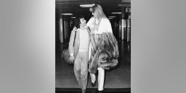 Comedian and actor Dudley Moore with his arm around his girlfriend Susan Anton, arriving at Heathrow Airport, London, October 1, 1980.