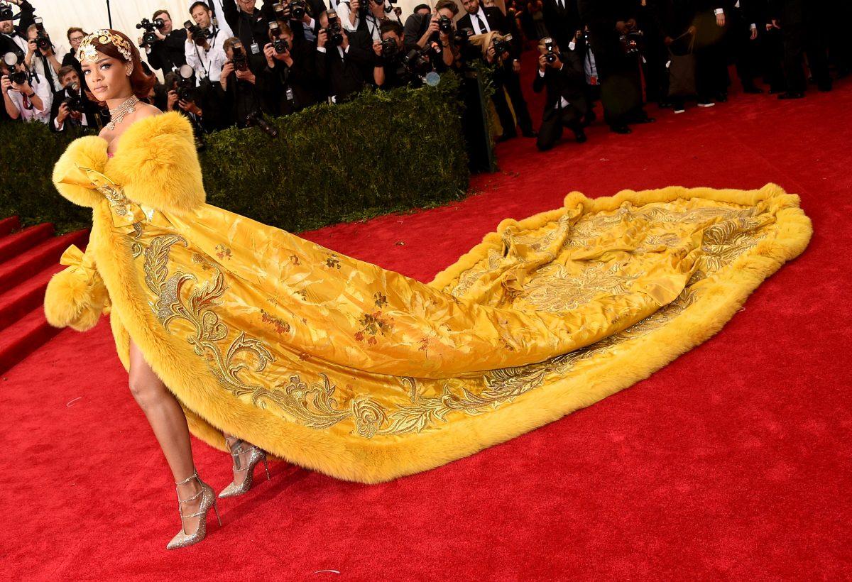 Rihanna posing in a yellow dress at the 2019 Met Gala.