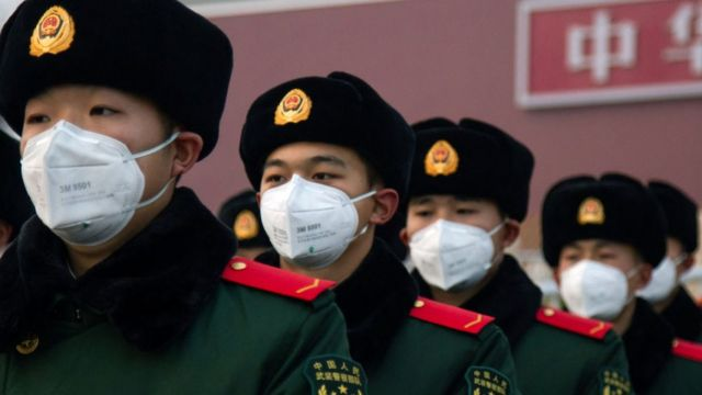 Chinese soldiers with masks in front of Tiananmen.