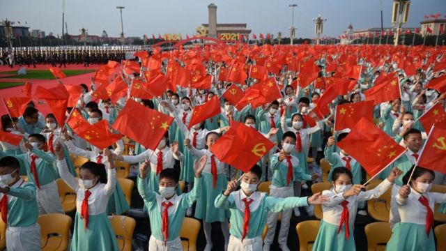 Students wave Chinese and CCP flags in Beijing on July 1, in Tiananmen Square.