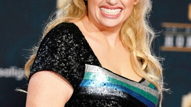 Rebel Wilson comes out of the water in a low-cut black swimsuit - Photo E! News UK
