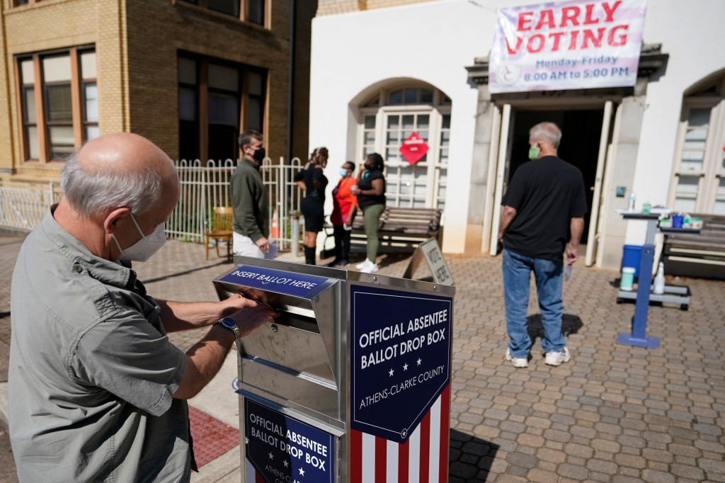 A voter sends a ballot to an official mailbox during early voting in October 2020.