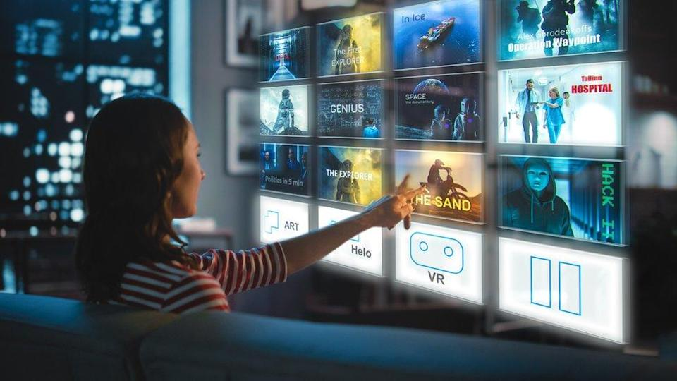 A woman selects programs on a virtual TV screen